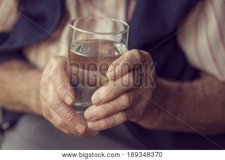Close up of an elderly woman's hands holding a glass of water