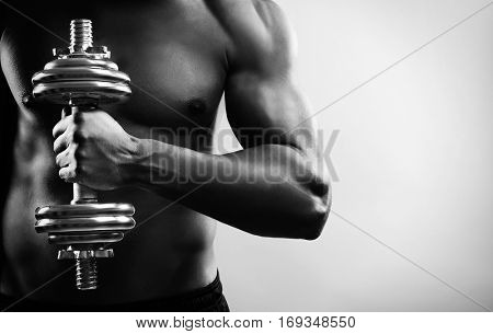 Man training with dumbbell. Black and white photo