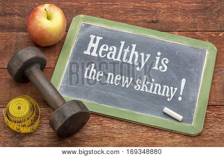 Healthy is the new skinny concept -  slate blackboard sign against weathered red painted barn wood with a dumbbell, apple and tape measure