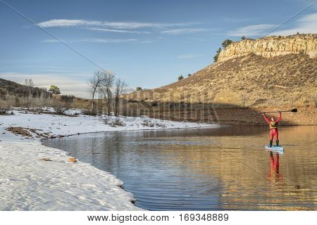 senior male paddler in drysuit  is enjoying stand up paddling on lake in Colorado, winter scenery