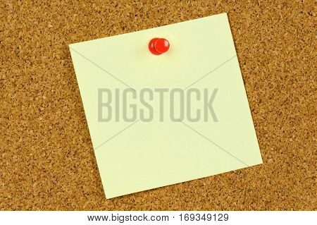 Blank yellow sticky note held on a cork notice board with a red pushpin.