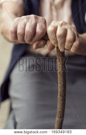 Detail of an elderly woman's hands holding a cane. Selective focus