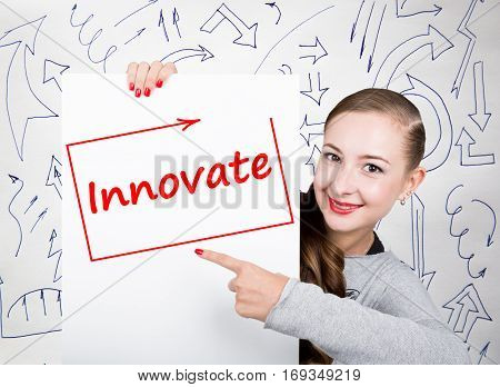 Young woman holding whiteboard with writing word: innovate. Technology, internet, business and marketing