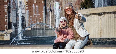 Mother And Daughter Tourists In Milan, Italy Showing Thumbs Up