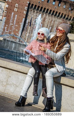 Mother And Daughter Tourists Holding Map And Pointing