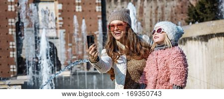 Mother And Daughter Travellers With Digital Camera Taking Selfie