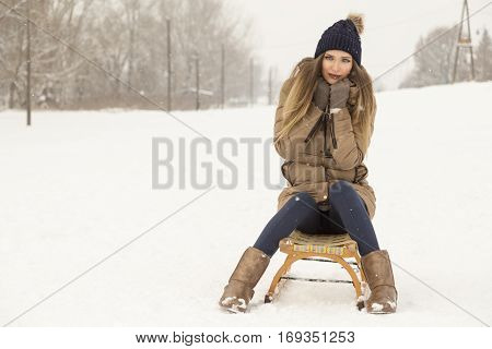 Beautiful young woman wearing a warm winter clothes and sitting on a sleight on a snowy winter day