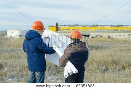 Engineers at a construction site with drawings in hand