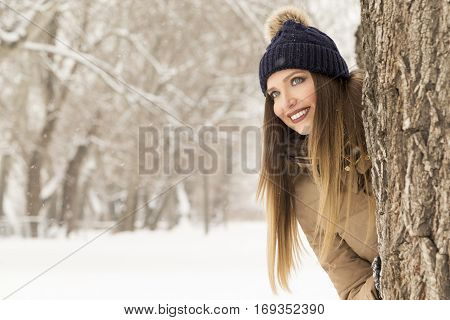 Beautiful woman smiling and peeking behind a tree enjoying a snowy winter day in nature