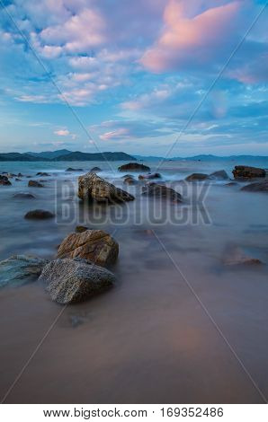 Rocky coastline on the south China sea off the coast of Vietnam with a colourful sky.