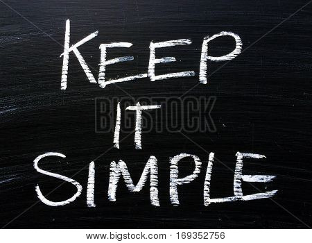 The words Keep It Simple written by hand in white chalk on a used blackboard as a reminder