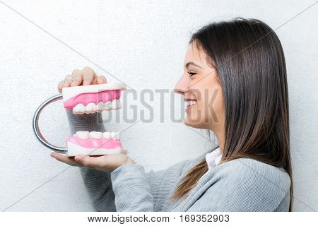 Close up portrait of attractive young girl holding oversize human teeth prosthesis.Side view of woman against light textured background.