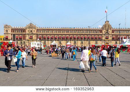 MEXICO CITY,MEXICO - DECEMBER 23, 2016 : People at the Zocalo or Constitution Square on a beautiful day in Mexico City