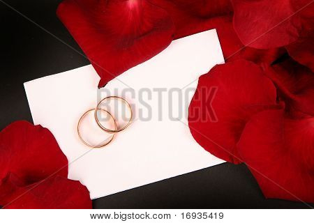 two wedding rings and red petals