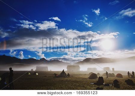 Travel to Iceland. Beautiful Icelandic landscape with mountains, sky and clouds. Trekking in national park Landmannalaugar. Morning in Camping near Alftavatn lake. Tents and hikers in the camping. Travel concept.
