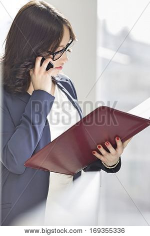 Young businesswoman using cell phone while reading file in office