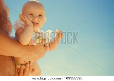 Closeup of happy sweet little baby in parent hands. Babyhood and parenting.