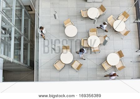 Blurred motion of businesswomen walking at office canteen