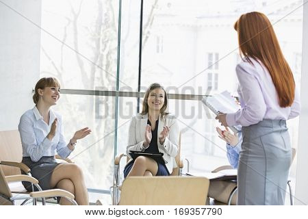 Happy businesswomen clapping for colleague after presentation in office