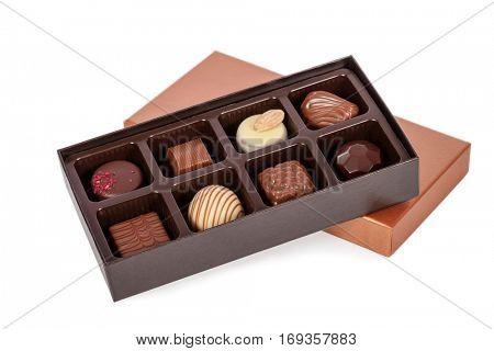 Box of gourmet bonbons, aka bon-bons and truffles made of dark, white and milk chocolate isolated on white background