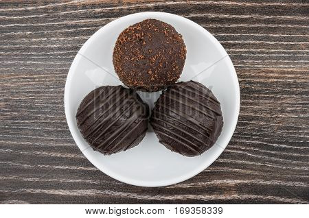Three Round Chocolate Cake In Glass Saucer On Dark Table