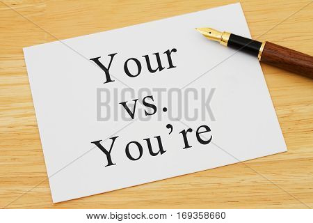Learning to use proper grammar A white card on a desk with a pen with words Your vs You're
