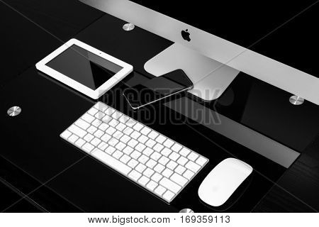 UKRAINE, RIVNE, January 2, 2017. Apple Computer iMac 27 retina display 5K keyboard and magic mouse and iphone, ipad, on black table.