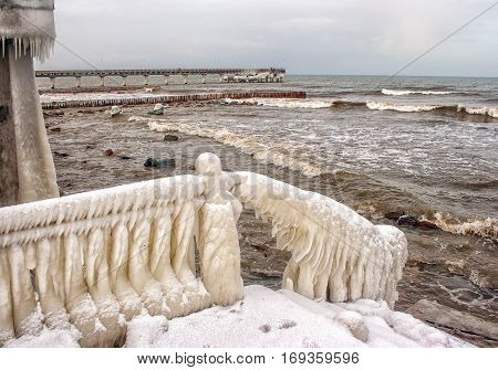 ice covered staircase on the beach on cold gloomy winter day