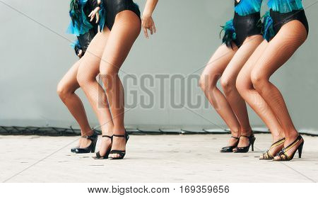 legs of four dancing women in brown stockings on stage outside
