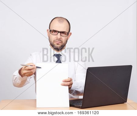 Please sign here. Portrait man in formalwear stretching out clipboard with paper and pointing it with pen while.Isolated on white background