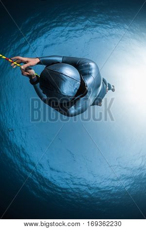 Underwater shot of the woman free diver hanging on the rope