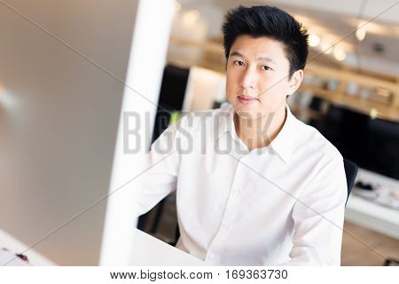 a young asian office worker is sitting at his desk. he could be a designer, programmer or a businessman.