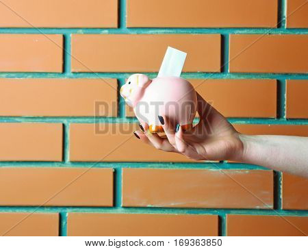 pink piggy bank or moneybox with paper in female hand on textured brick wall background as savings symbol copy space