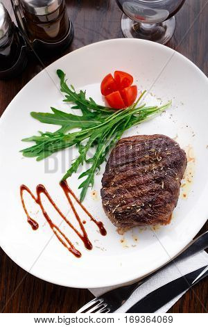 Medium grilled beefsteak on a plate with cherry tomato and arugula