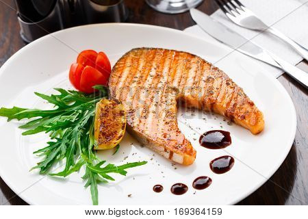 Grilled salmon steak with cherry tomato and arugula