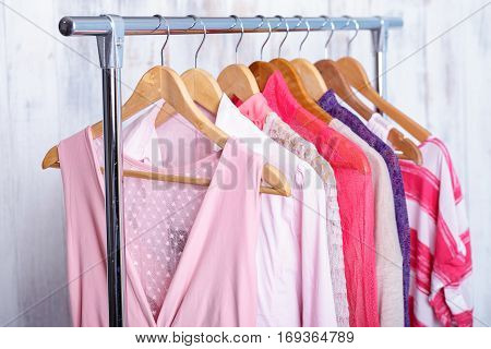pink womens clothes on wood hangers on rack in a fashion store. . closet women dresses, blouses