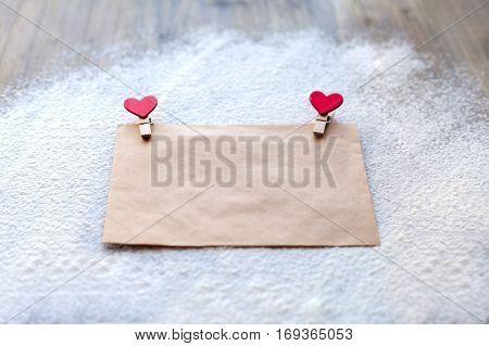 The envelope of Kraft paper with two red clothespins in the shape of hearts Valentine's day people's attitudes.