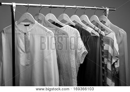 black and white photo of womens clothes on hangers on rack. closet of woman