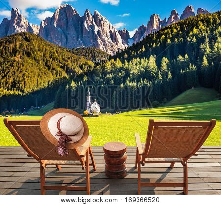 Two deck chairs on a wooden floor installed to relax and review the Alpsg and church of Santa Magdalena. The concept of eco-tourism in Alpine meadows