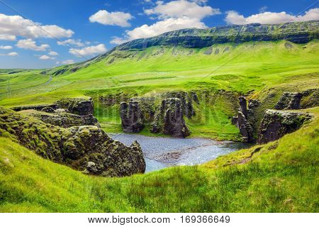 The striking canyon in Iceland. Green Tundra in July. The concept of active northern tourism. Bizarre shape of cliffs surround the stream with glacial water