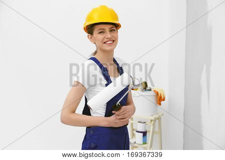 Beautiful young decorator in empty room