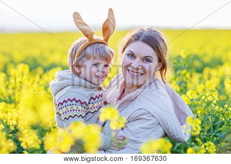 Little toddler child and his mother in Easter bunny ears having fun, celebrating traditional Easter holiday. Kid toddler boy and mum, woman In yellow rape field, outdoors