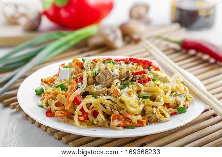 Traditional oriental food made of rice noodles vegetables shiitake and tofu. Asian meal.
