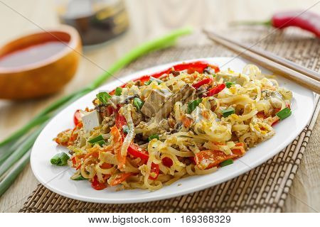 Asian food. Fried rice noodles with tofu vegetables and shiitake mushroom. Oriental cuisine meal.
