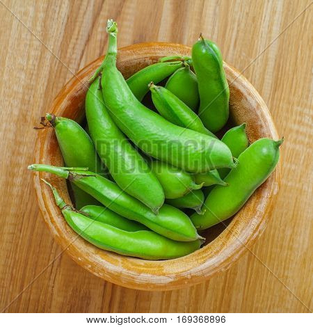 Bowl of fresh podded broad beans on a wooden table. Healthy organic food.