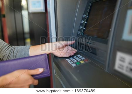 finance, money, bank and people concept - close up of hands with wallet withdrawing cash at atm machine
