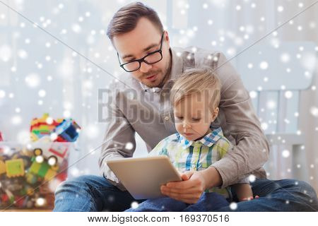family, childhood, fatherhood, technology and people concept - happy father and son with tablet pc computer playing at home over snow