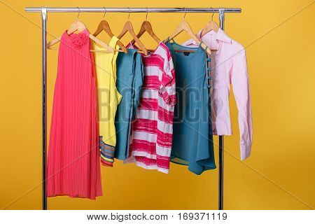colorful womens clothes on wood hangers on rack on orange background. women's closet