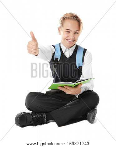 Teenage boy with backpack and book sitting on white background