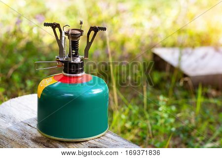 Touristic camping burner installed on gas cylinder tank in background of summer forest. Compact kitchen stove for cooking hot food in field travel conditions. Adventure Park poster